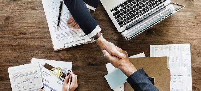 Two gentlemen giving a handshake to each other on a table after their company registration.