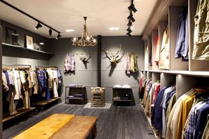 An interior of an apparel store with some apparels hanging and some decor pieces on the wall.